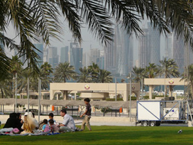 Doha residents relax on the Corniche a day off from the office. The Westbay can be seen in the distance